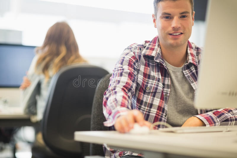Cheerful student looking at camera in the computer room royalty free stock photography