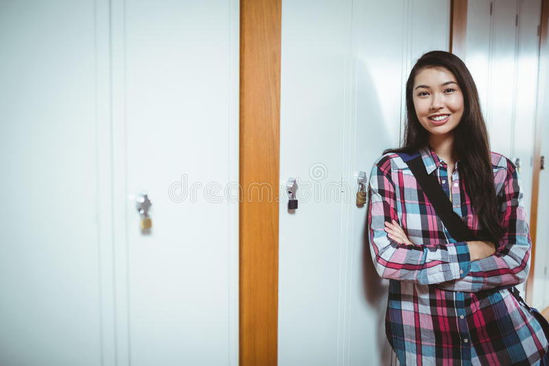 Cheerful student standing next the locker stock image