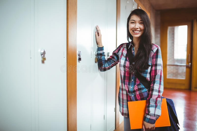 Cheerful student standing next the locker stock photography