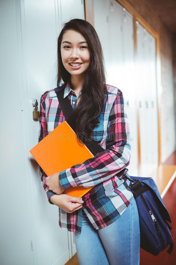 Cheerful student standing next the locker stock photos