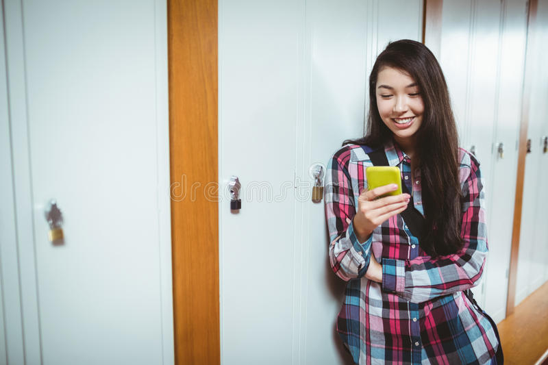 Cheerful student standing next the locker and using smartphone royalty free stock images