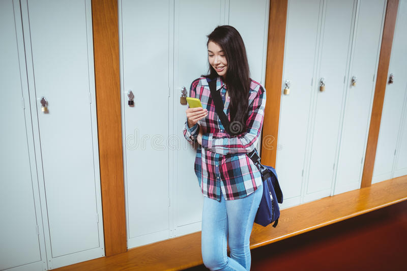 Cheerful student standing next the locker and using smartphone royalty free stock photos
