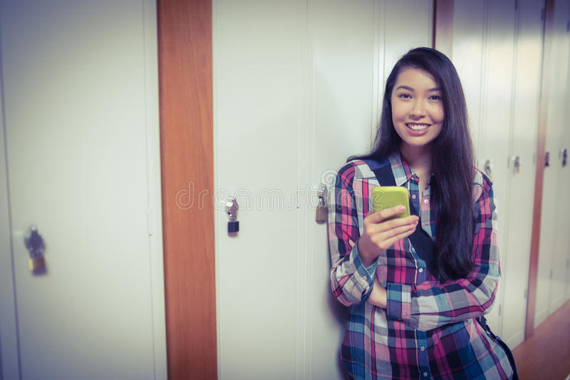Cheerful student standing next the locker and using smartphone stock photography