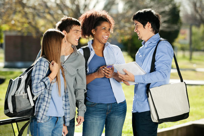 Cheerful Students Looking At Friend In Campus royalty free stock photography
