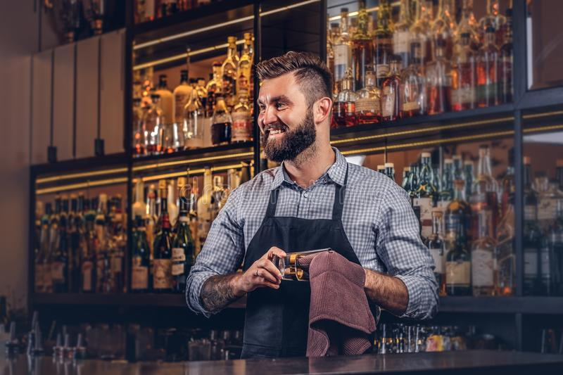 Cheerful stylish brutal barman is cleaning the glass with a cloth at bar counter background. Cheerful stylish brutal barman is cleaning a glass with a cloth at stock photos