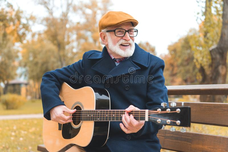 Cheerful stylish senior man playing on acoustic guitar. In autumn park royalty free stock photography