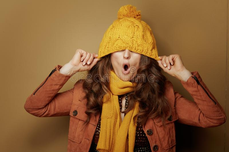 Cheerful stylish woman with beret over eyes on brown background royalty free stock photos