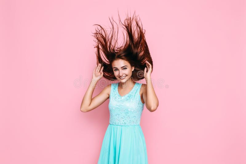 Cheerful woman in a bright dress, waving her hair, having fun on a pink background. Cheerful stylish woman in a bright dress, waving her hair, having fun on a royalty free stock images