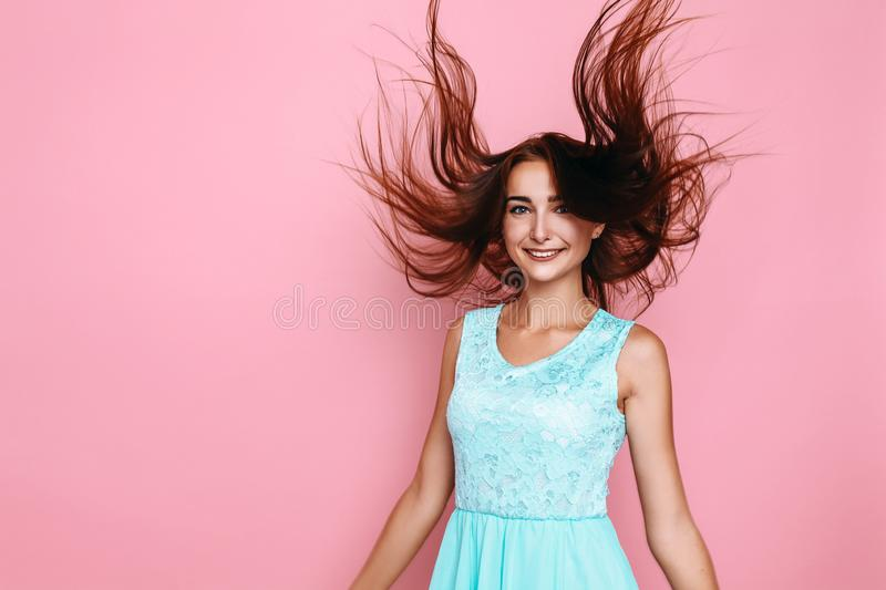 Cheerful woman in a bright dress, waving her hair, having fun on a pink background. Cheerful stylish woman in a bright dress, waving her hair, having fun on a stock photo