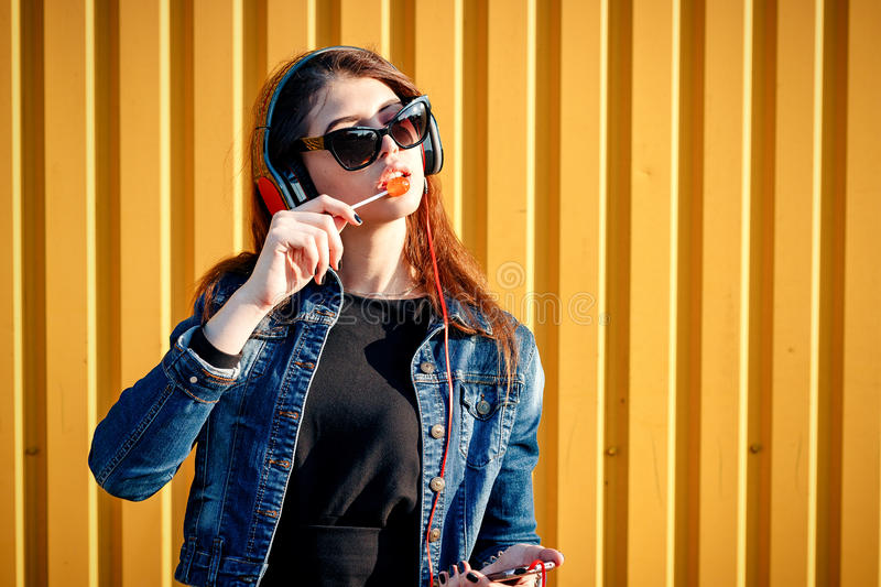 Cheerful stylish young girl in jeans jacket, headphones with phone, wearing sunglasses, listening to music by the yellow wall on royalty free stock images