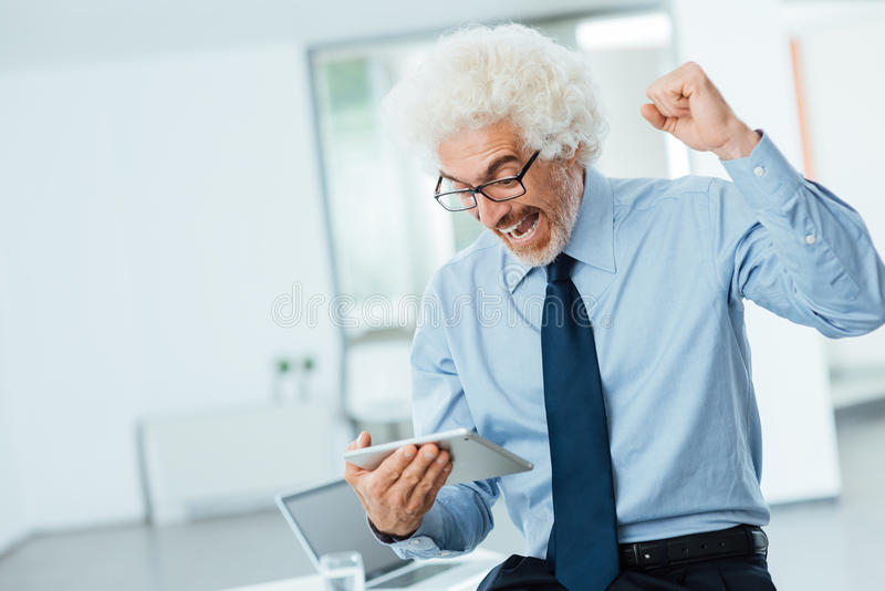 Cheerful successful businessman receiving good news stock photography