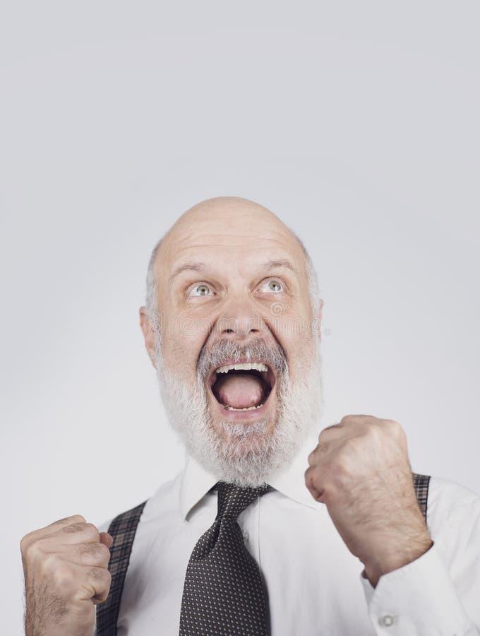 Cheerful successful senior businessman celebrating stock photography