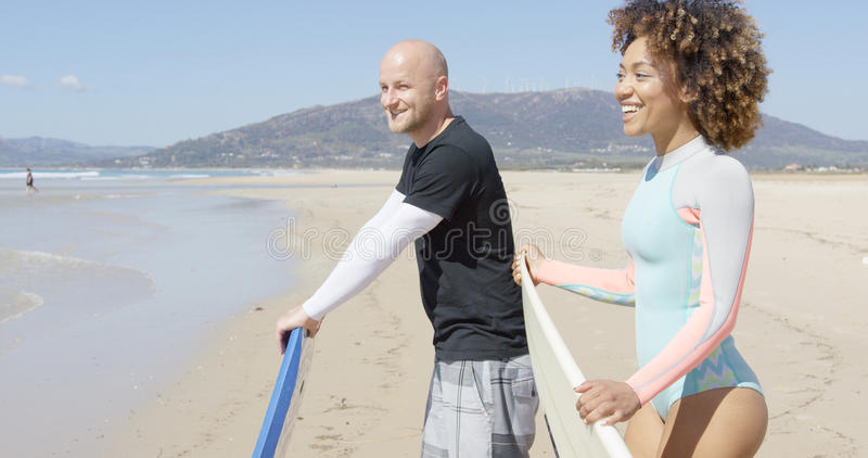 Cheerful surfers on a beach stock photography