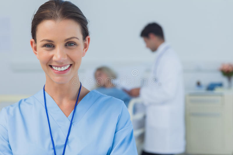 Cheerful surgeon posing with doctor attending patient on background stock photos