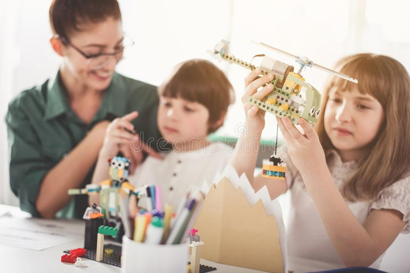 Cheerful teacher and kids playing with toys. Outgoing lady talking with boy. Glad children having fun with constructor. Positive education concept stock photos