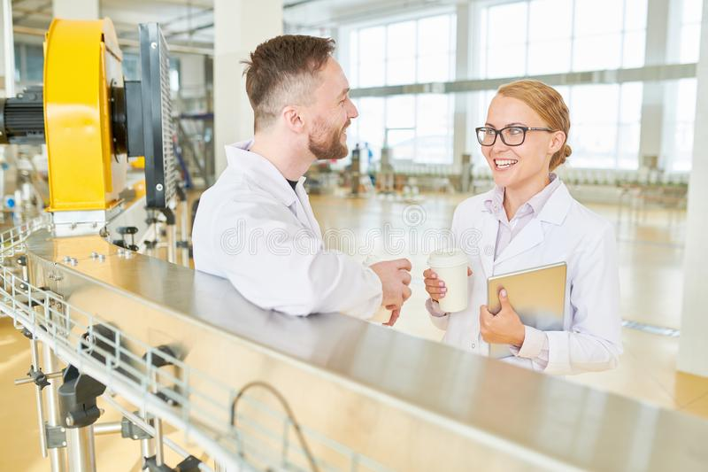 Technologists Taking Coffee Break. Cheerful technologists wearing white coats chatting animatedly with each others while taking coffee break at spacious stock photography