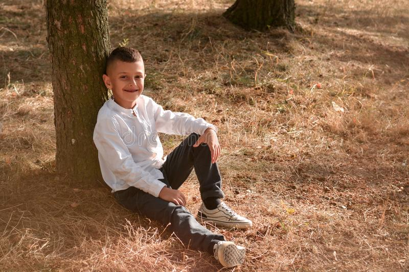 Cheerful teen boy sitting under a tree stock photo