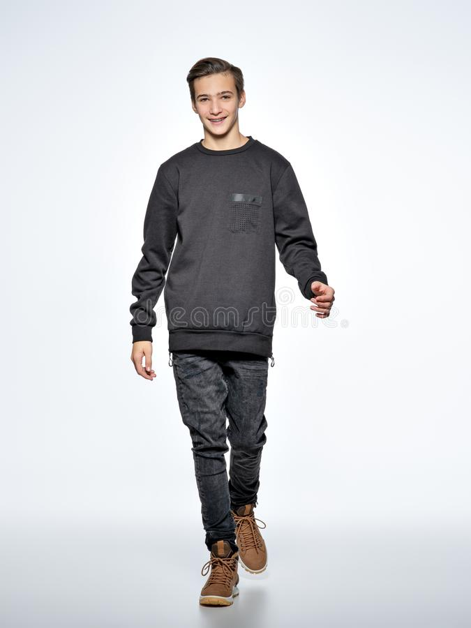 Cheerful teenage boy dressed in black trendy clothes posing at s royalty free stock photos