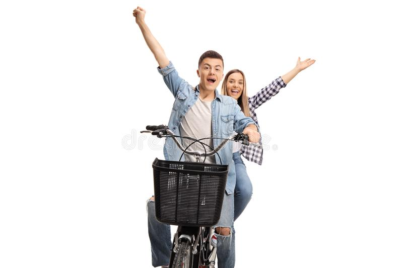 Cheerful teenage boy and girl riding on a bike and raising hands royalty free stock photos