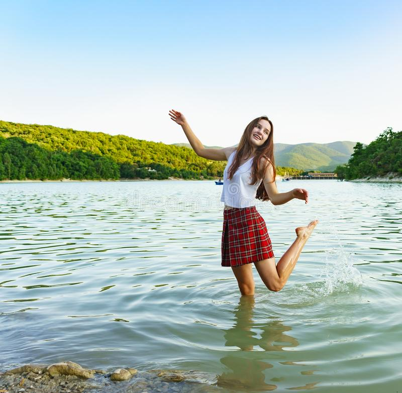 Cheerful teenage girl dancing knee-deep in lake Sukko in the mountains royalty free stock photography