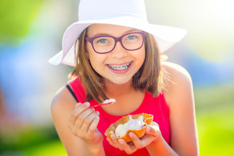 Cheerful teenage girl with dental braces glasses and ice cream. Portrait of a smiling pretty young girl in summer outfit with ice stock photography