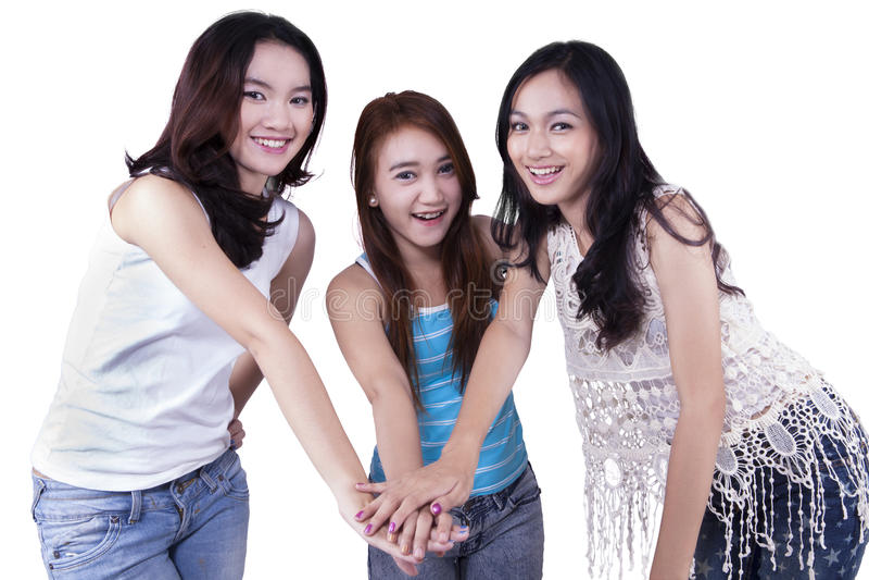 Cheerful teenage girls joining hands stock image