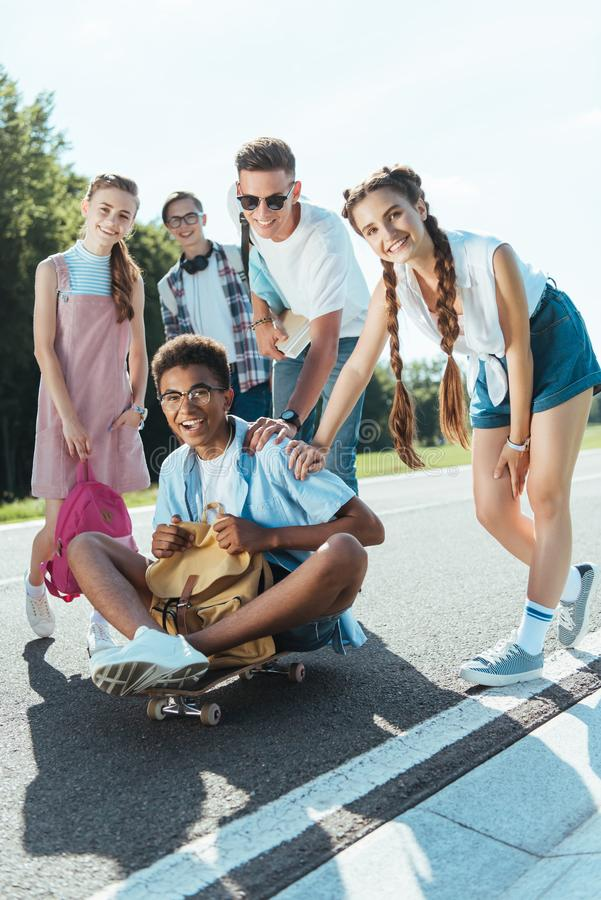 cheerful teenage multiethnic classmates with books and backpacks smiling at camera while having fun with skateboard stock photography