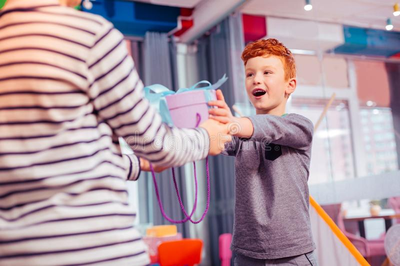 Cheerful teenager visiting party of his friend. Birthday party. Handsome red-haired boy expressing positivity while giving present stock images