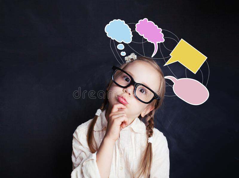 Cheerful thinking child girl with speech clouds bubbles royalty free stock photos