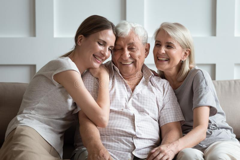 Cheerful three-generation family sitting on couch enjoy time together. Happy three-generation family hugging sit on sofa enjoy time together at home, laughing royalty free stock image