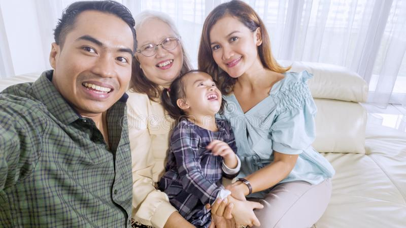 Cheerful family takes a group picture at home. Cheerful three generation family sitting on the sofa while taking a group selfie picture at home royalty free stock image