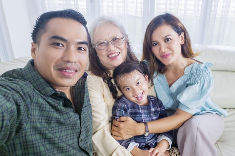 Cheerful three generation family takes selfie at home stock image