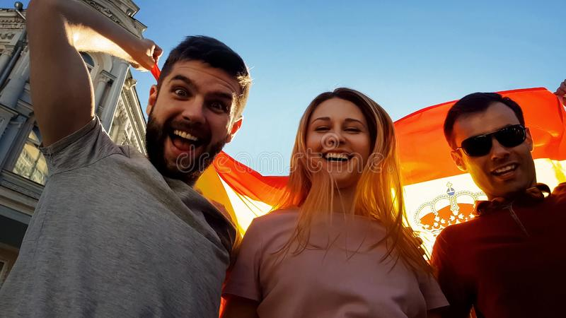 Cheerful tourists from Spain posing for camera on background of national flag stock photography