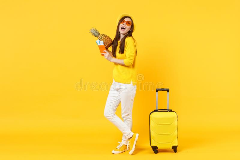 Cheerful traveler tourist woman in hat holding passport tickets, fresh pineapple fruit isolated on yellow orange. Background. Passenger traveling abroad on royalty free stock photography
