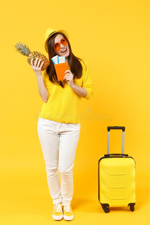 Cheerful traveler tourist woman in hat holding passport tickets, fresh pineapple fruit isolated on yellow orange. Background. Passenger traveling abroad on stock image