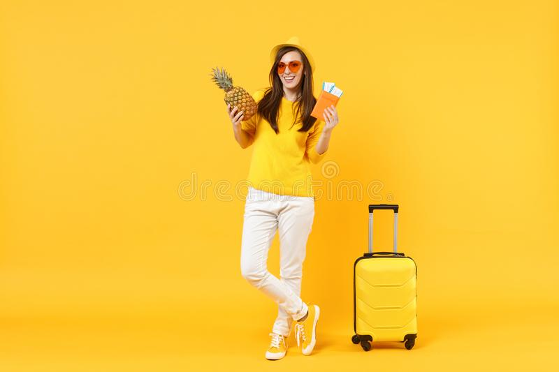 Cheerful traveler tourist woman in hat holding passport tickets, fresh pineapple fruit isolated on yellow orange. Background. Passenger traveling abroad on royalty free stock photo