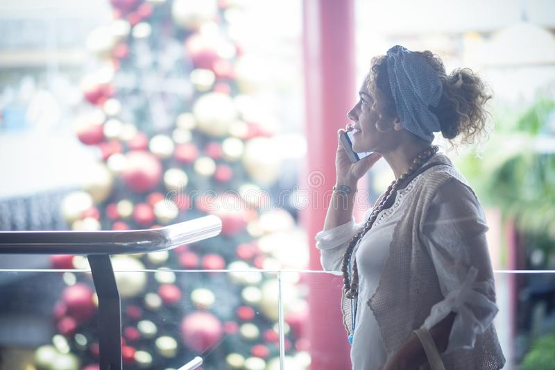 Cheerful trendy caucasian lady phone calilng in commercial center with christmas tree and lights in background - xmas time in the royalty free stock image