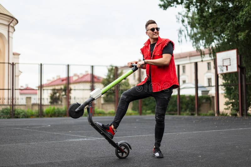 Cheerful trendy young man holds a modern scooter behind the wheel and raises up. Positive stylish hipster guy with smile. Riding an electric scooter around the royalty free stock image