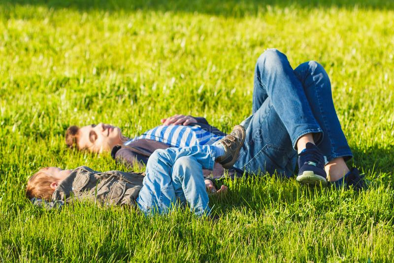 Cheerful two brothers lie on the grass in the park and play in funny games stock photography