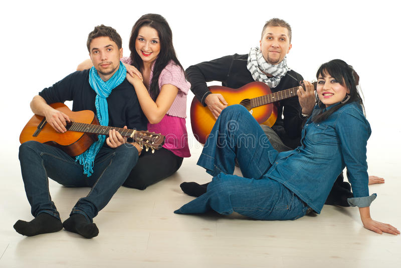 Cheerful two couples with guitars. Cheerful two couple sitting on wooden floor and the guys playing acoustic guitars stock images
