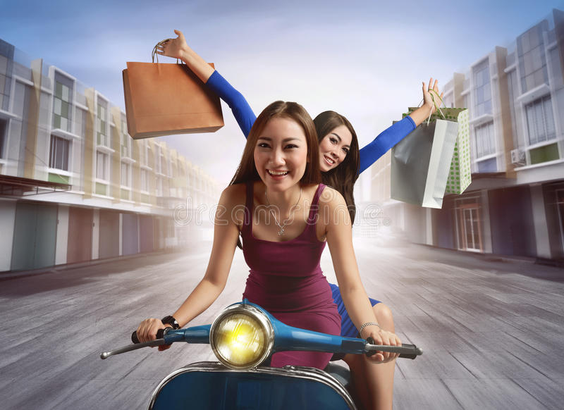 Cheerful two young asian woman with shopping bag riding a scooter royalty free stock photography