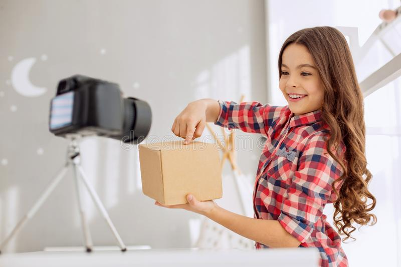 Cheerful video blogger making guesses about box content. Burning curiosity. Adorable pre-teen girl in a checked shirt pointing at the box in her hands and making stock images
