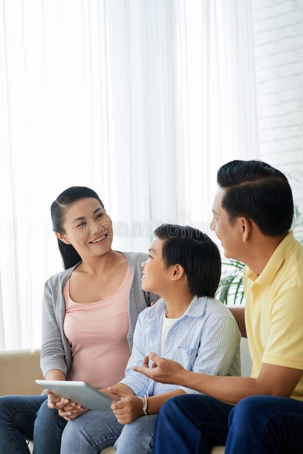 Family discussing application. Cheerful Vietnamese family sitting on sofa and discussing new application on tablet computer royalty free stock photos