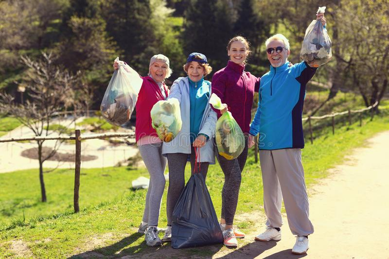Cheerful volunteers holding packets with litter. Amazing team. Happy fit volunteers smiling and holding packets with litter royalty free stock images
