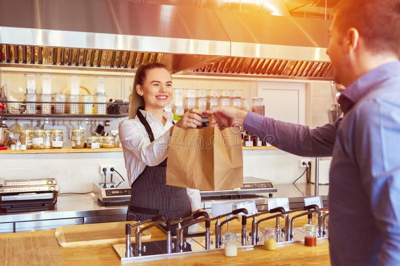 Cheerful waitress wearing apron serving takeaway order to customer at counter in restaurant in eco friendly paper bag stock images