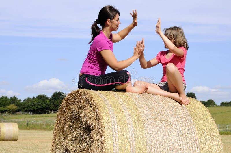 Cheerful white people having fun on hay bales royalty free stock photo