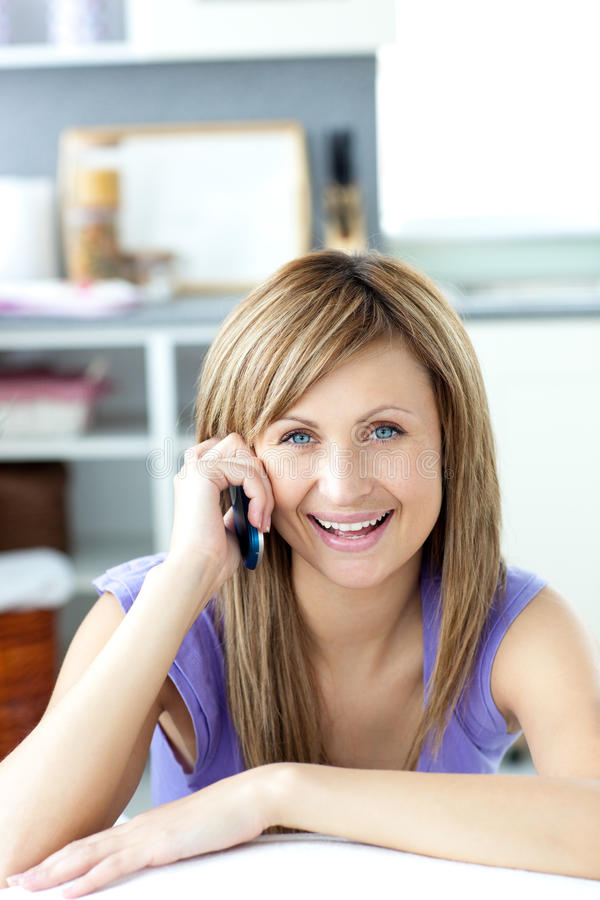 Cheerful woman answering the phone in the kitchen royalty free stock images