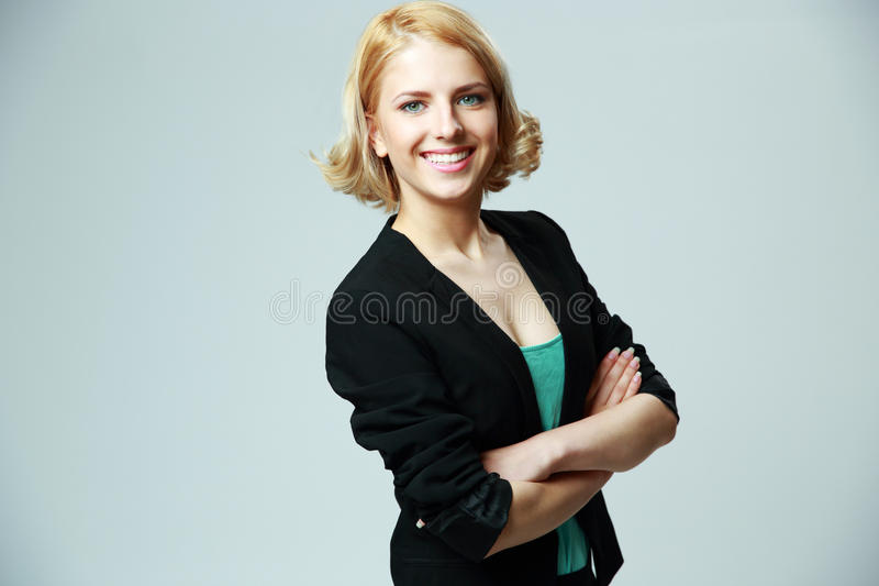 Cheerful woman with arms folded. Portrait of a young cheerful woman with arms folded on gray background royalty free stock photo