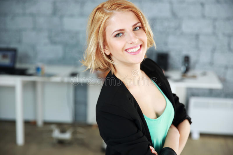 Cheerful woman with arms folded. Portrait of a young cheerful woman with arms folded in office stock images