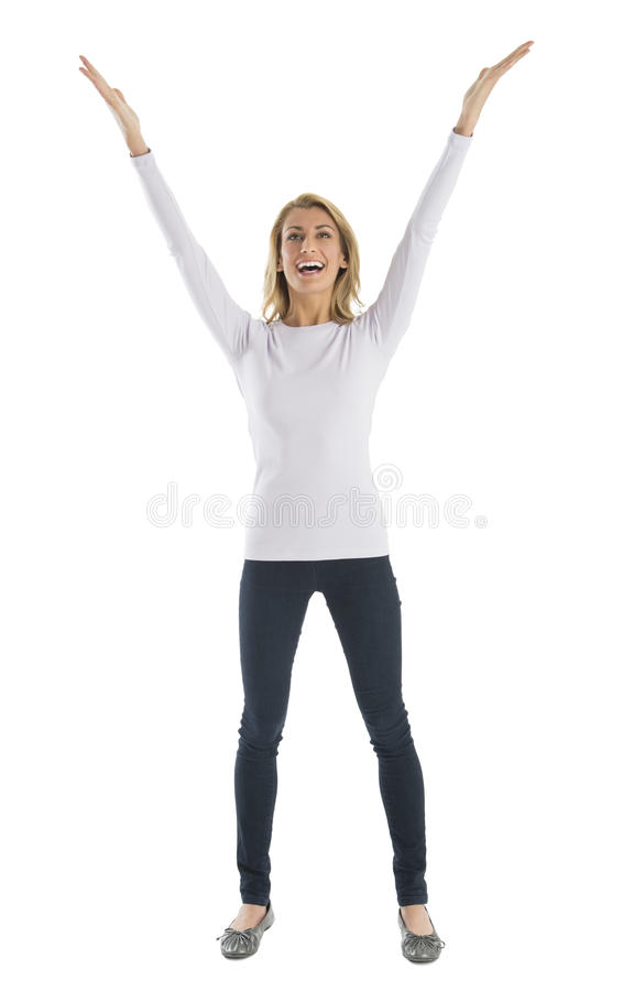 Cheerful Woman With Arms Raised Looking Away. Cheerful young woman with arms raised looking away while standing against white background royalty free stock photo
